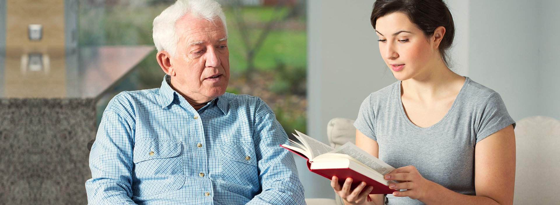 young woman reading books to an old man